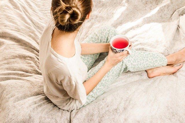 žena sedící na posteli s šálkem čaje